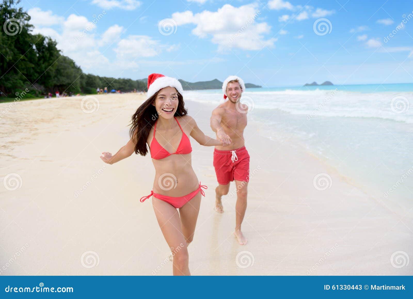 Relaxamento feliz dos pares do Natal no curso da praia