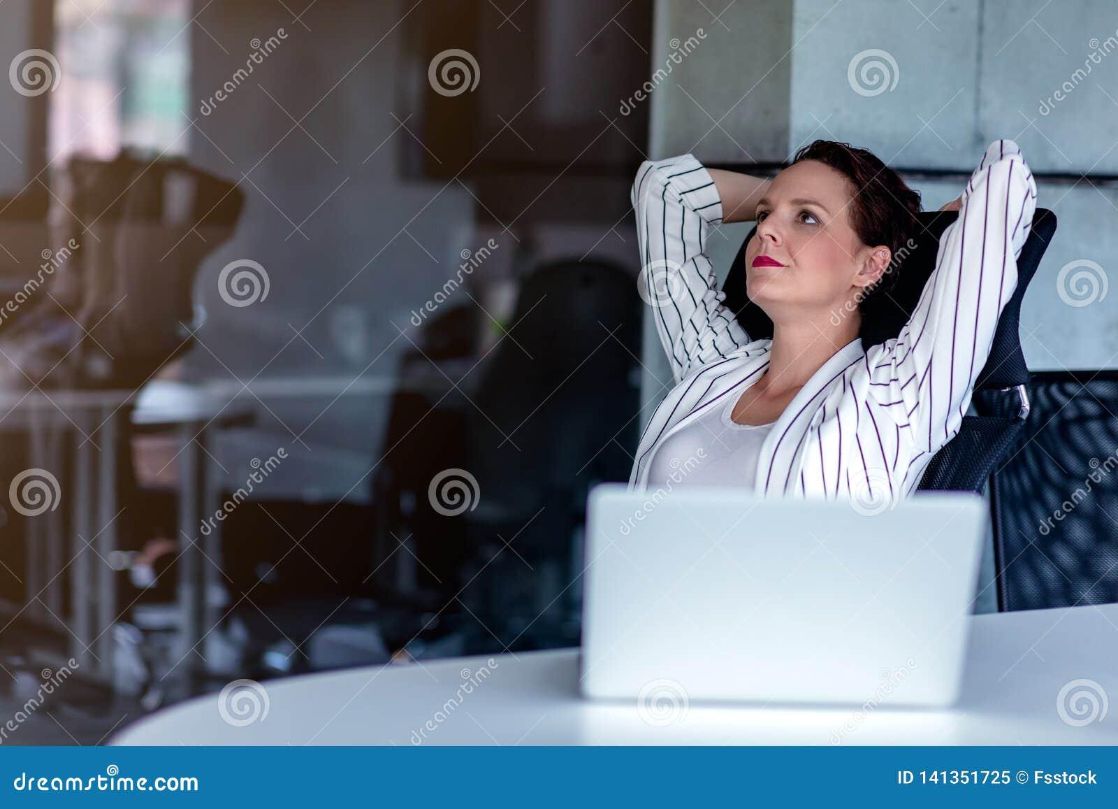 Relaxamento no lugar de funcionamento Jovem mulher atrativa que guarda as mãos atrás da cabeça e que mantém os olhos fechados ao