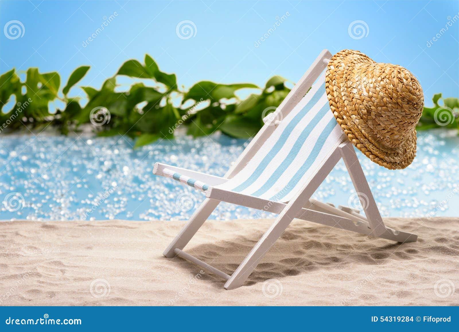 Relaxation à la plage avec le canapé du soleil et chapeau de soleil devant une lagune bleue