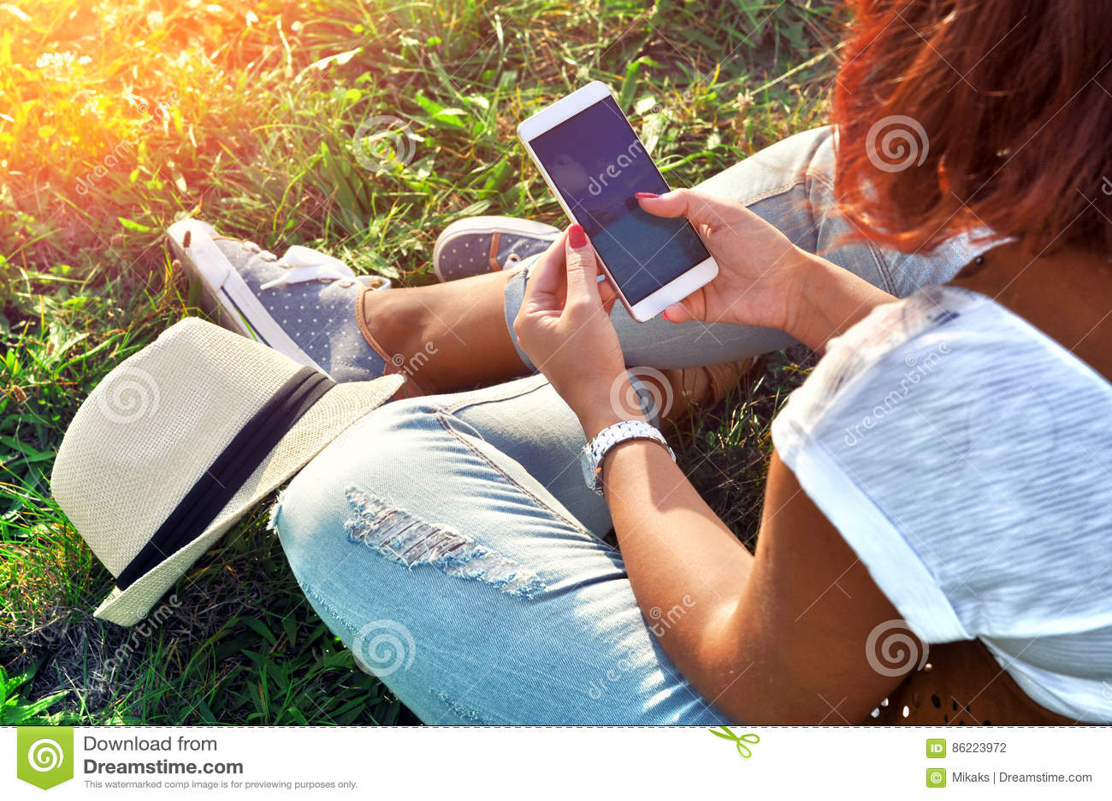Relaxation avec un mobile Temps de coupure Jeune femme à l aide du téléphone portable et se reposant sur l herbe