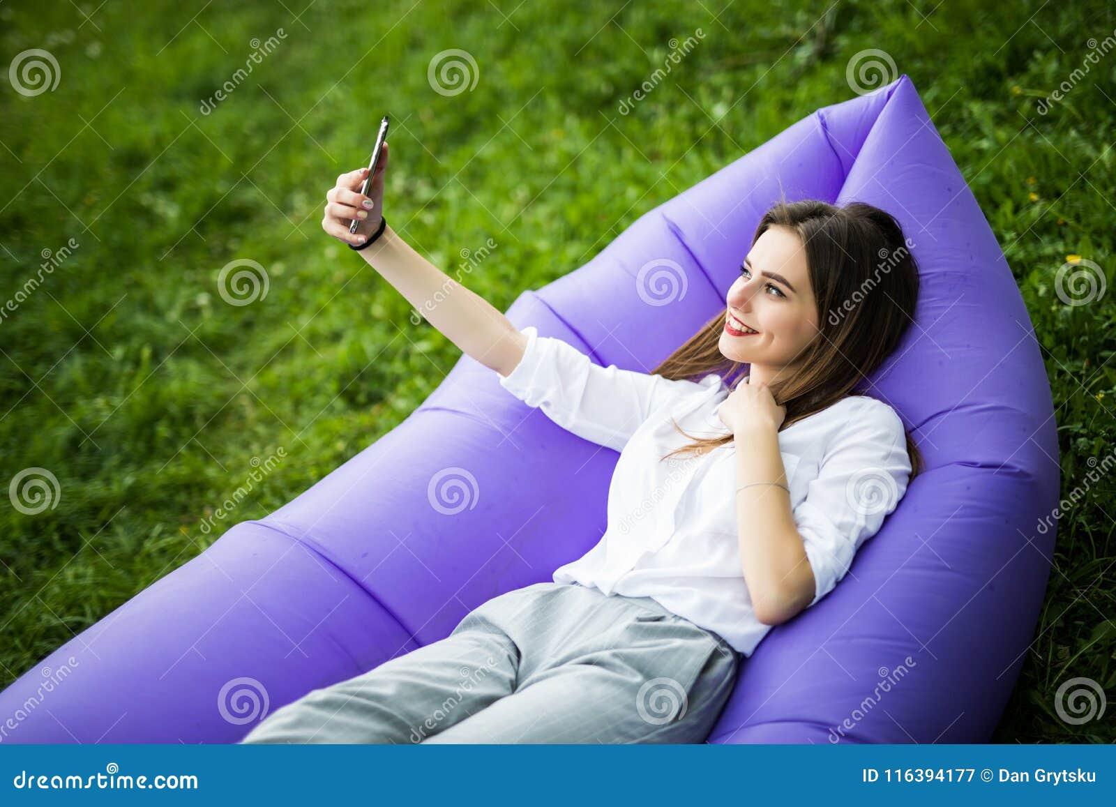 Relaxe no ar fresco Jovem mulher bonita que encontra-se no telefone celular inflável do uso do lamzac do sofá ao descansar na gra