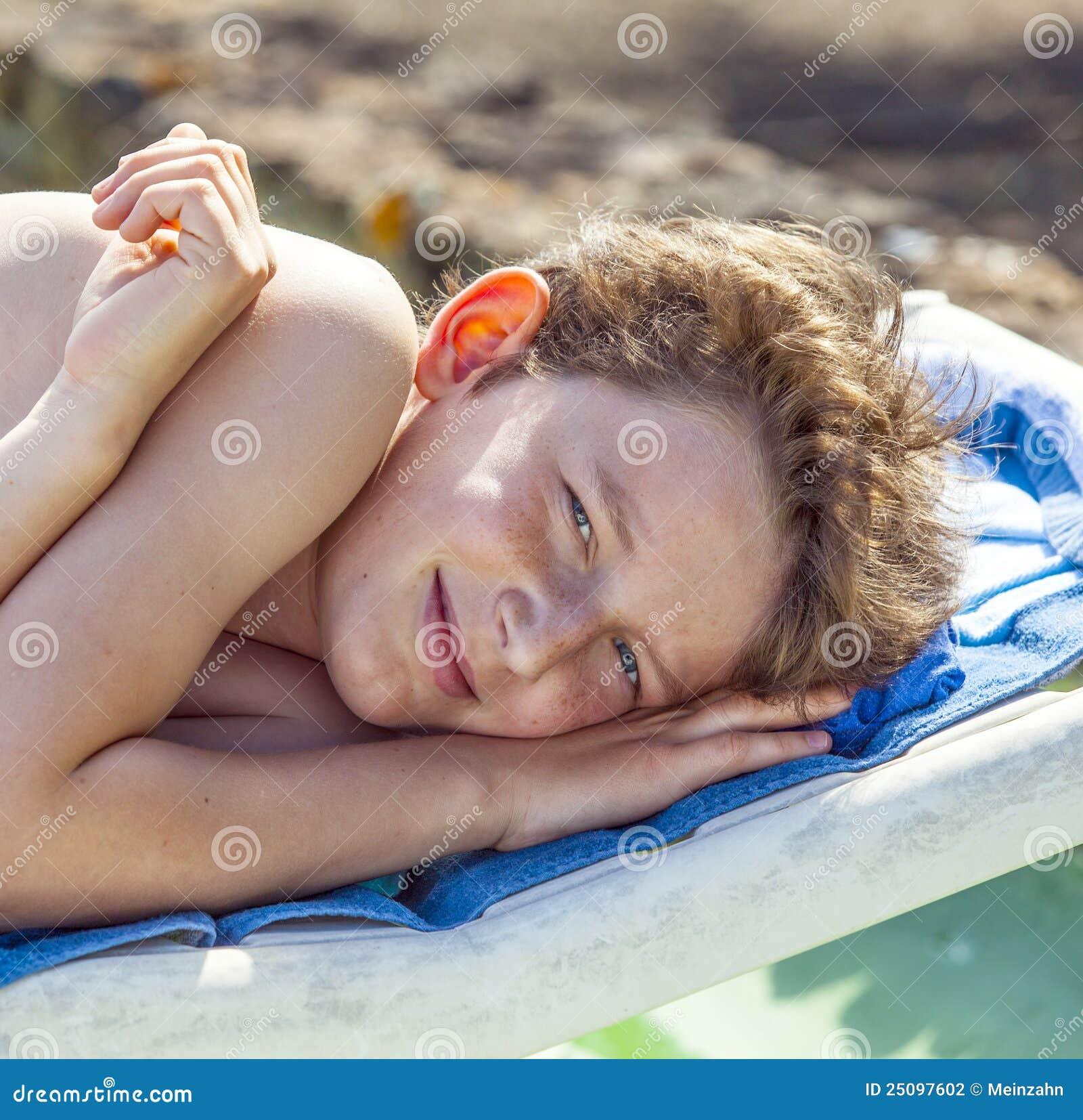 Relaxed Boy Enjoys Lying On A Beach Lounger Stock Photo