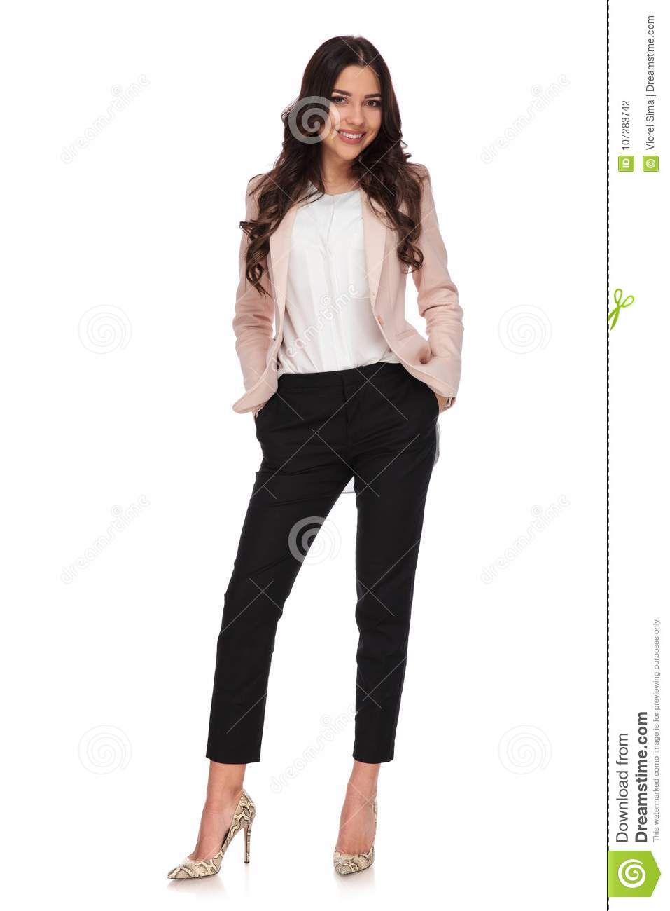 9d8d1f07548a Relaxed business woman standing with hands in her pockets on white  background