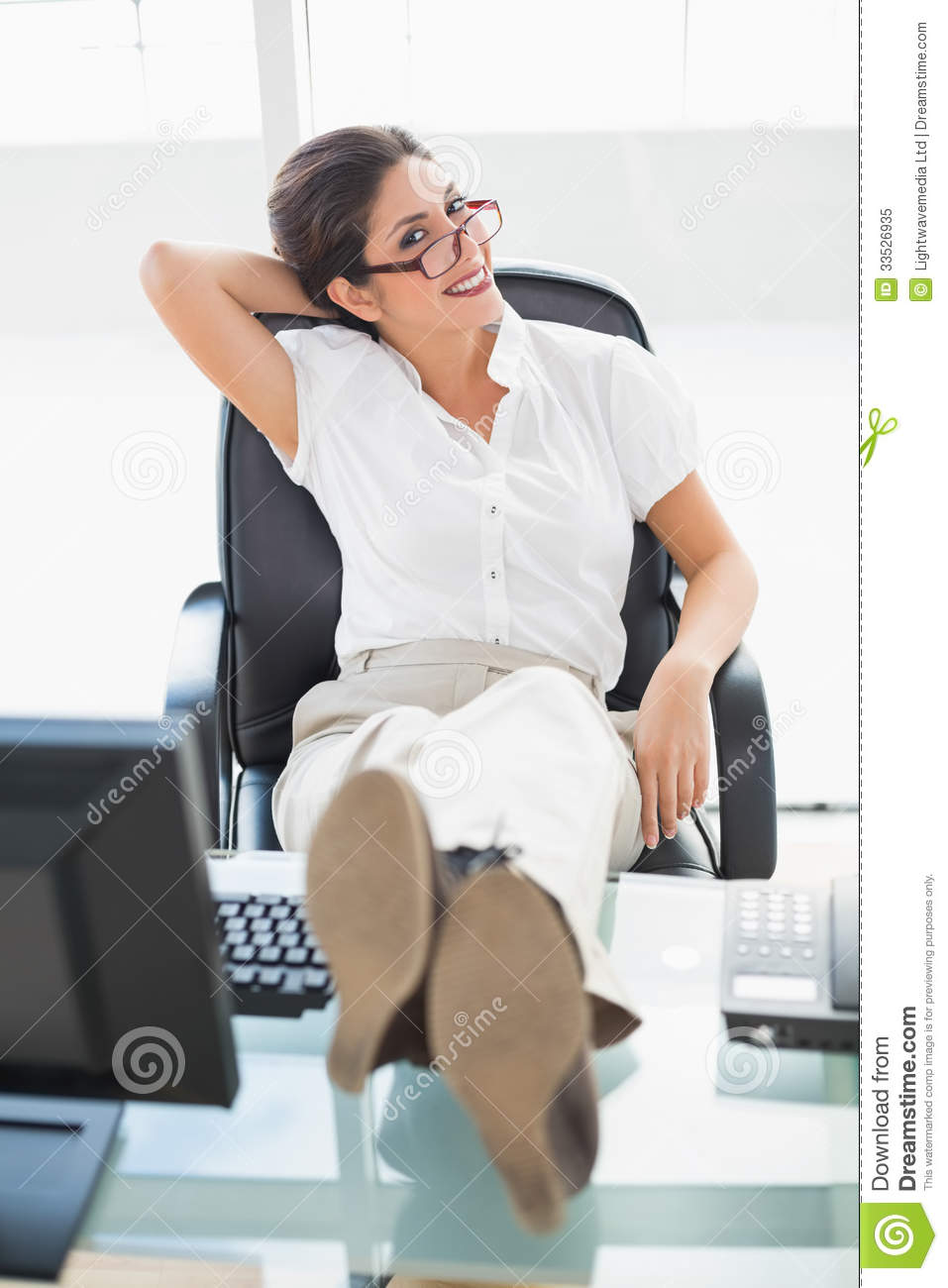 Relaxed Businesswoman Sitting At Her Desk With Her Feet Up
