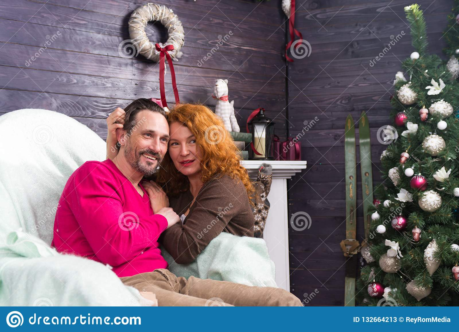 Relaxed couple smiling and looking into the distance during winter holidays
