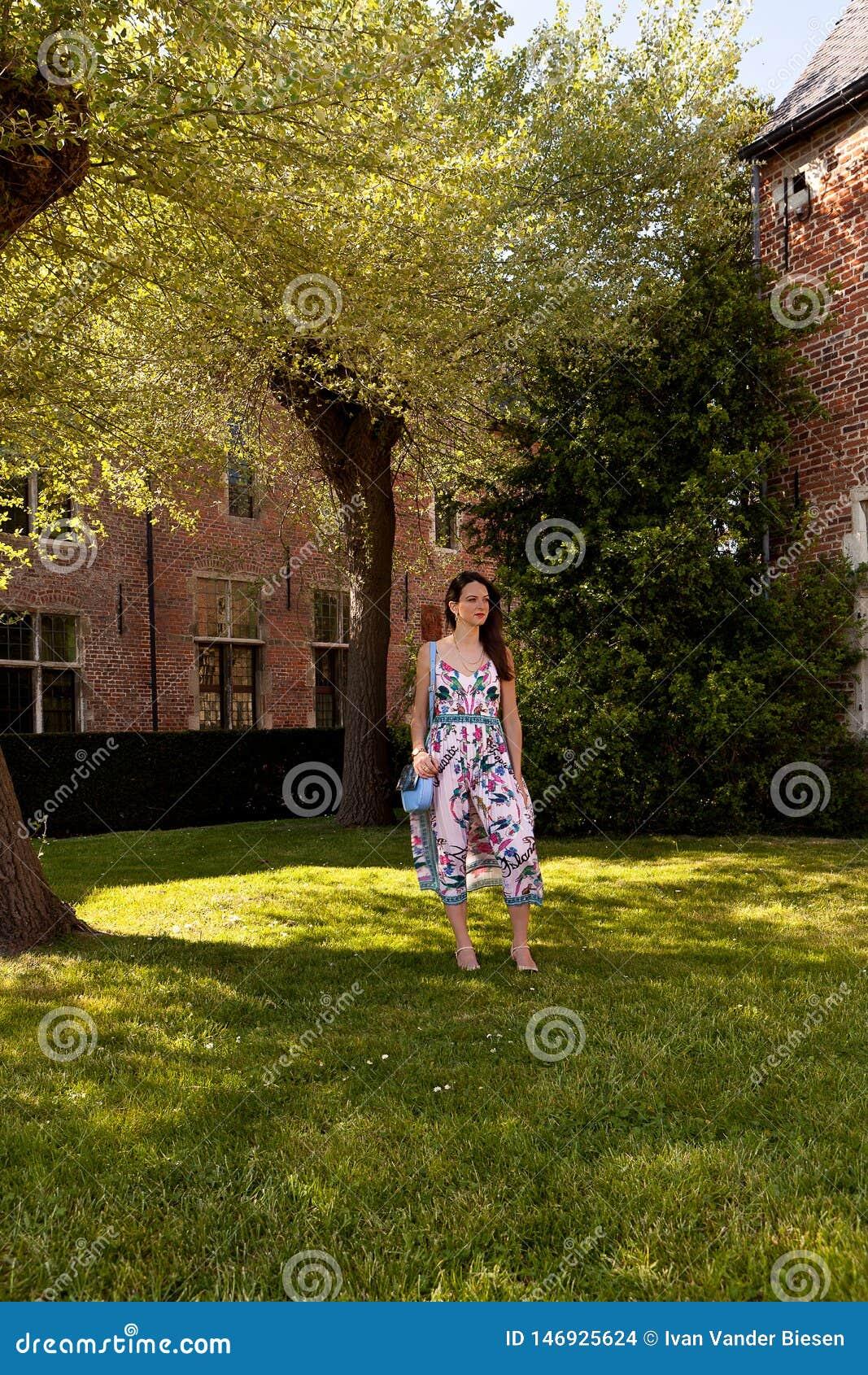 Relaxed woman standing grass tree, Groot Begijnhof, Leuven, Belgium