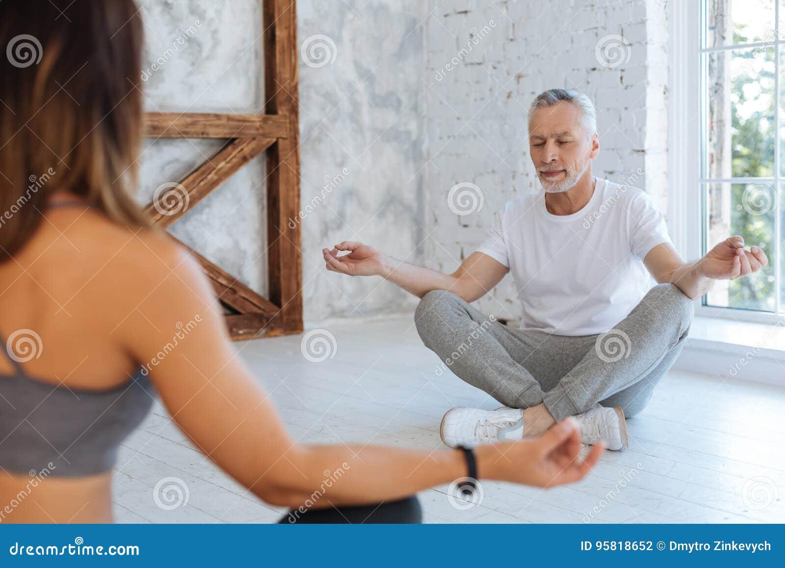Man sitting in yoga pose. stock image. Image of meditation