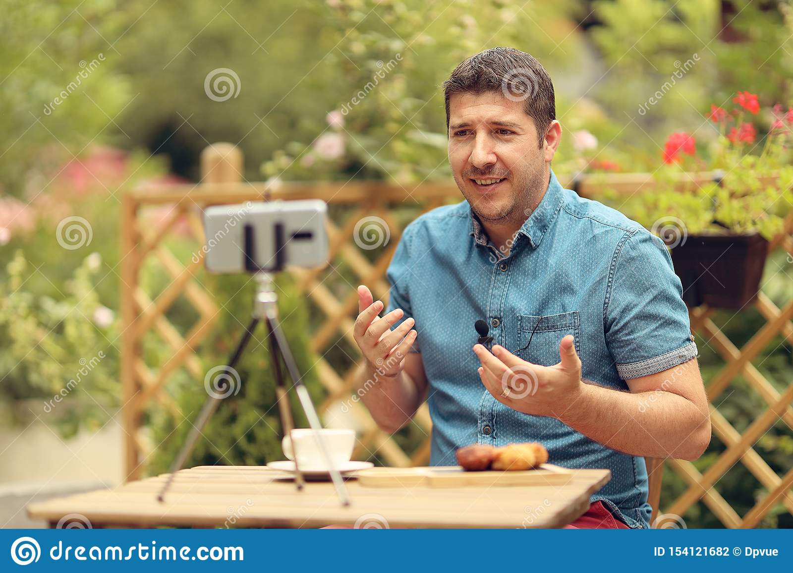 Relaxed manager discussing business strategies with his team on video call. Young casual business owner at a table having a video