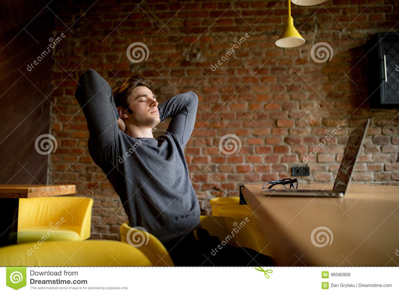 Relaxed mature businessman reclining at lobby on laptop