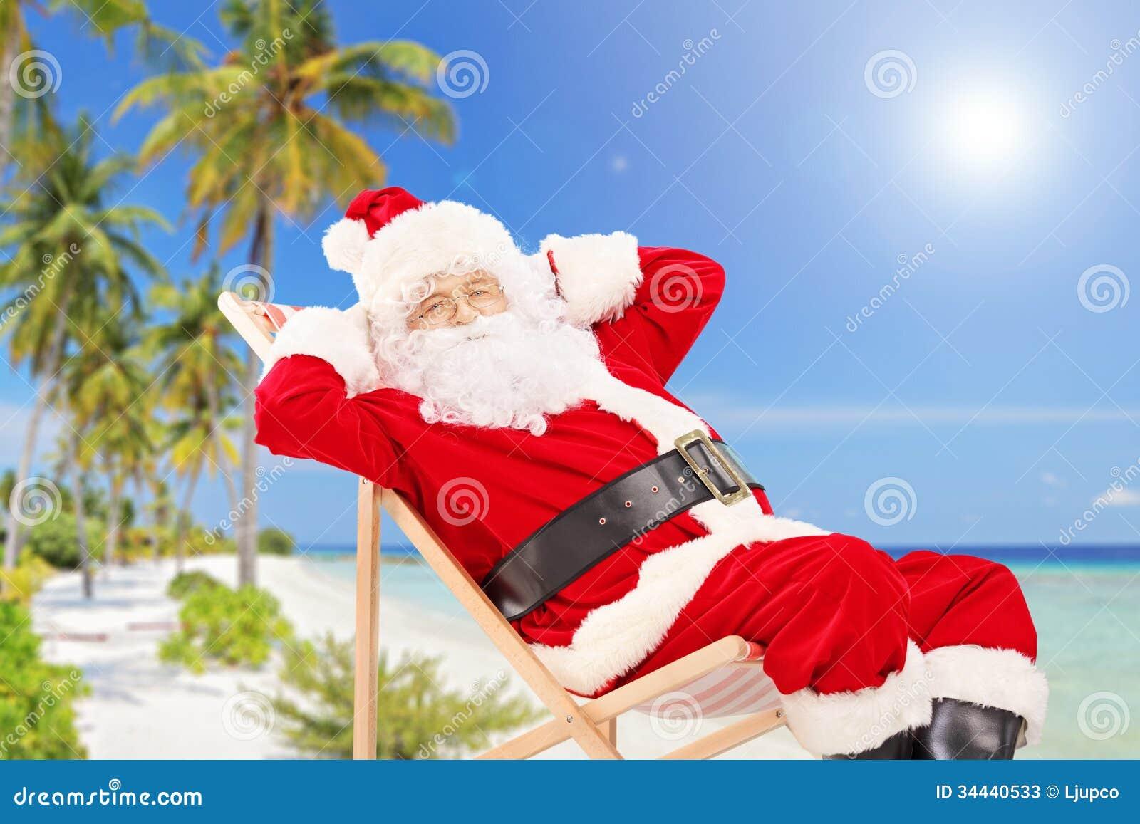 Relaxed Santa Claus sitting on a chair, on a tropical beach, enjoying ...