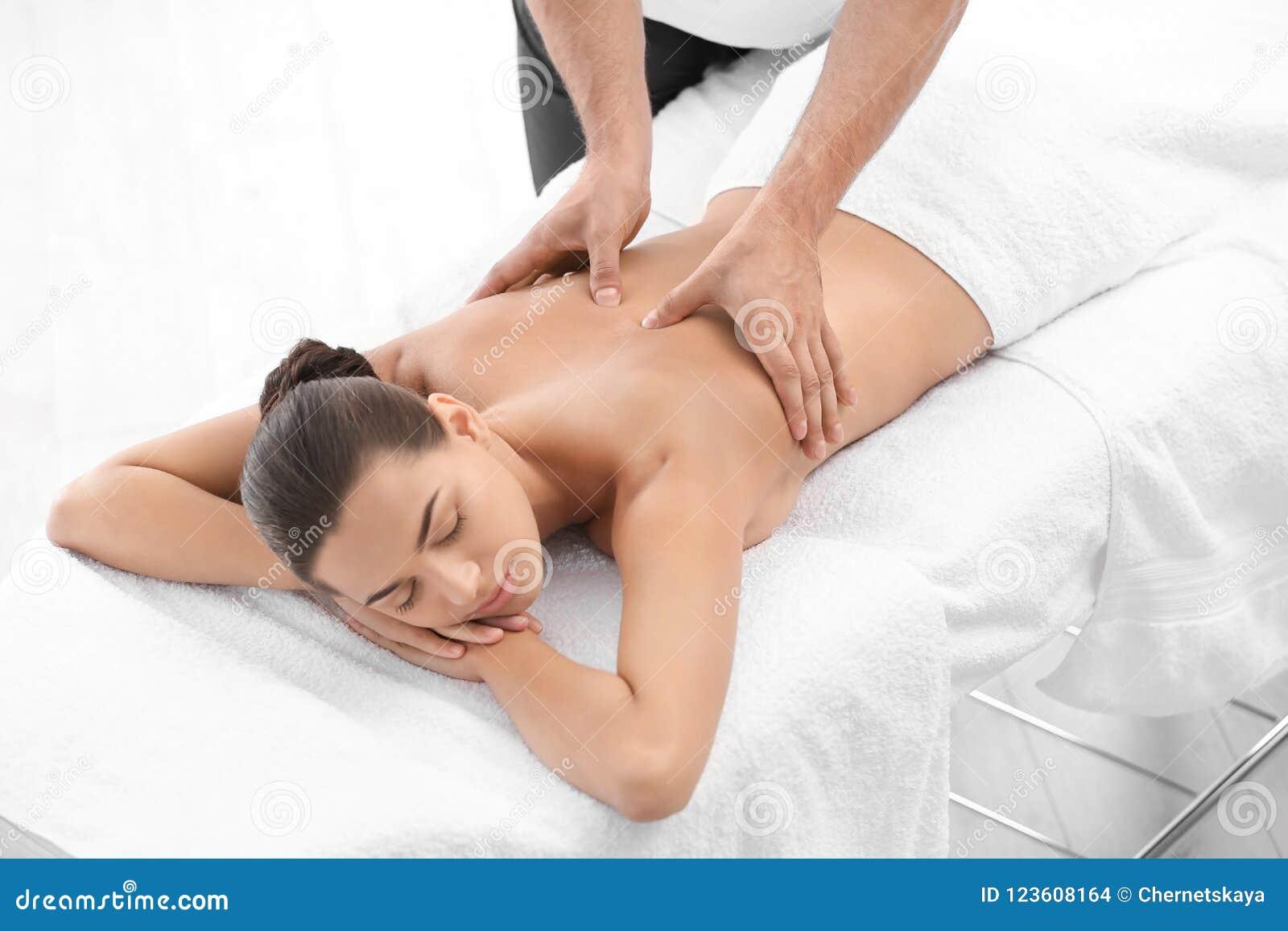 Relaxed woman receiving back massage d