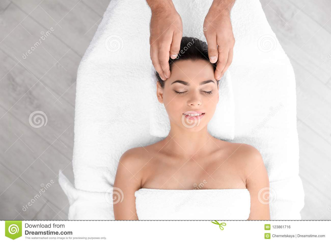 Relaxed woman receiving head massage