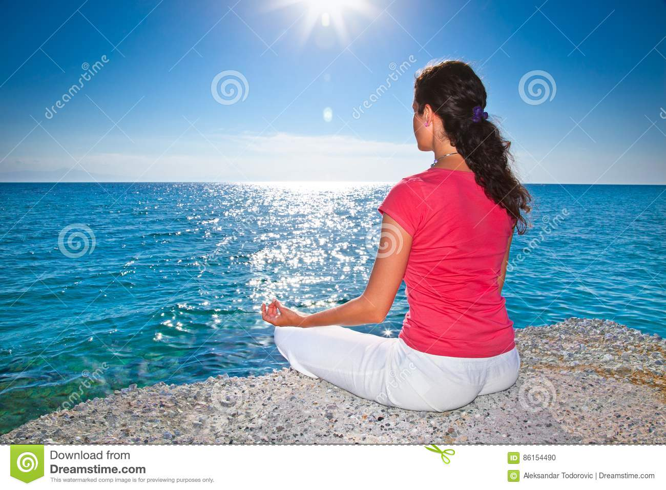 Relaxed woman sitting on a tropical beach at sunrise. Greece.