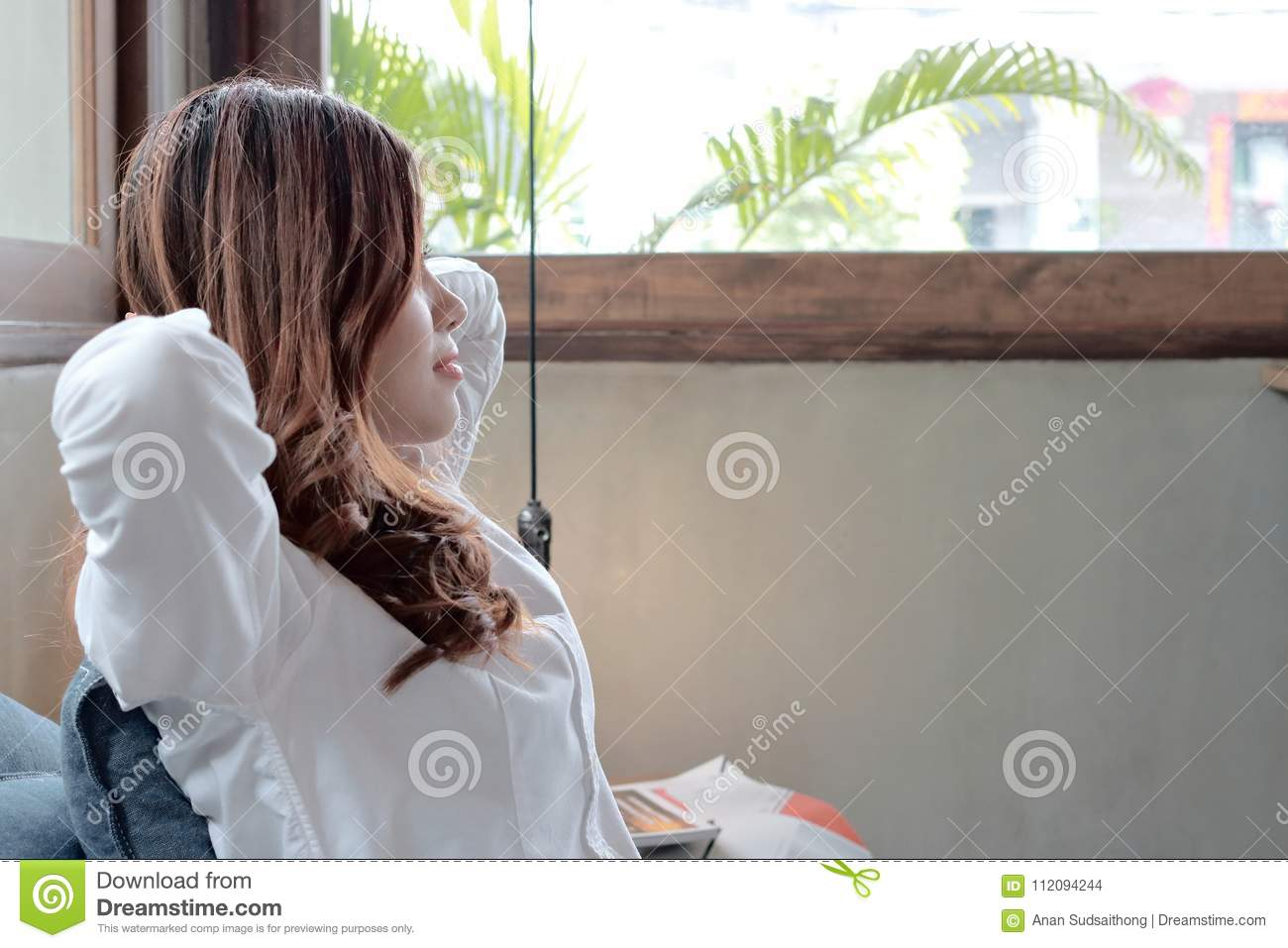 Relaxed young Asian woman sitting and looking through windows at far away in coffee shop against copy space background.