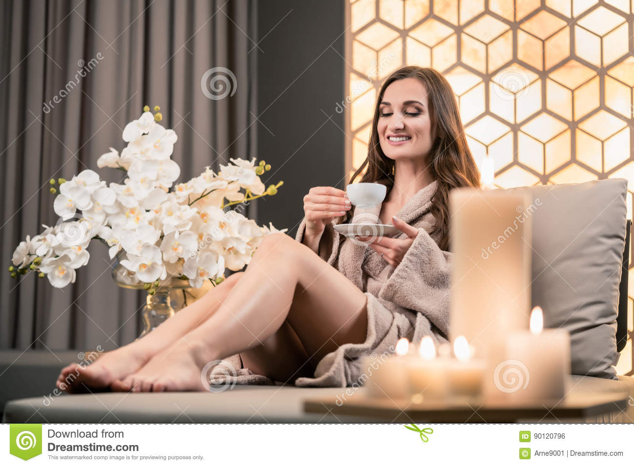 Relaxed young woman drinking herbal tea before spa treatment