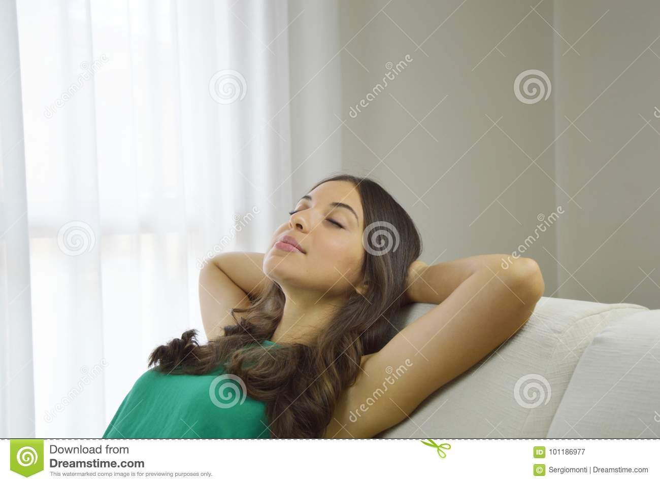 Relaxed young woman taking a nap on sofa. Smiling young woman with green tank top relaxing on a sofa at home sitting on a sofa in