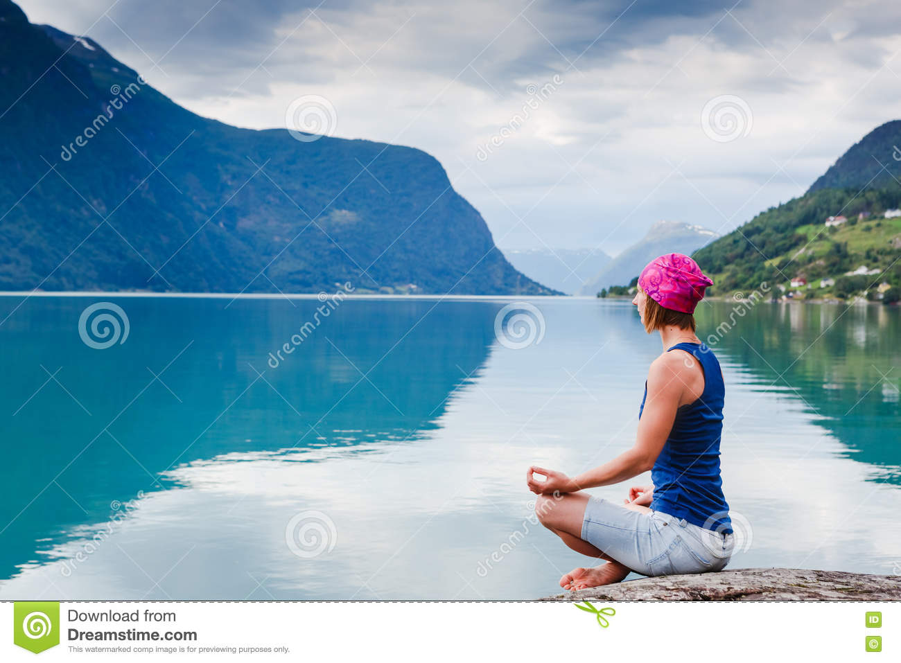 relaxed young yoga woman in yoga pose near the lake