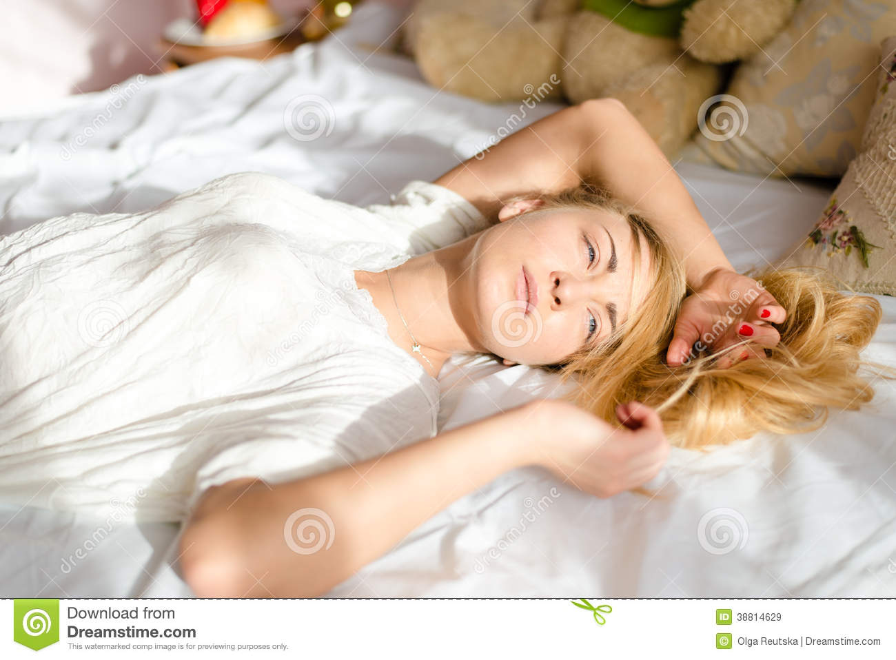 Relaxing attractive sincere young blond woman tender girl lying in bed in the sunlight