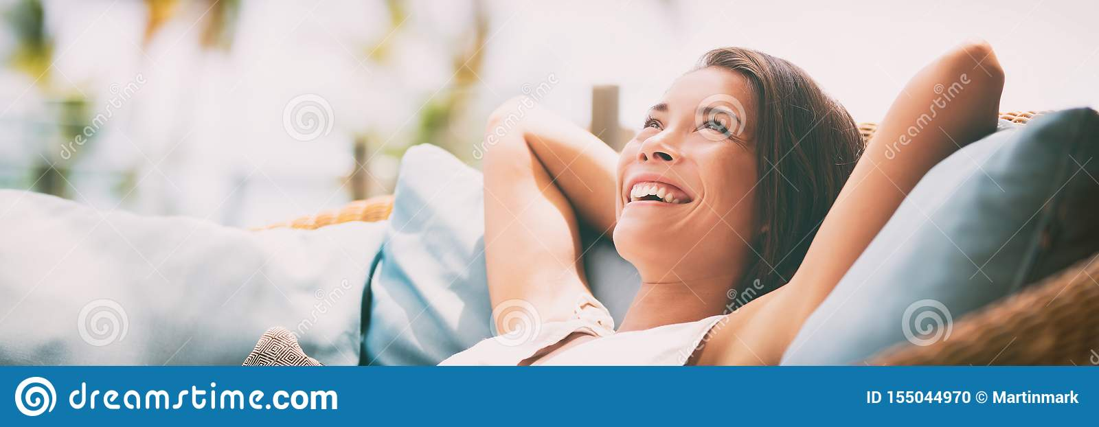 Relaxing home lifestyle happy woman in relax luxury hotel room sofa lying back with arms behind head smiling. Asian girl in