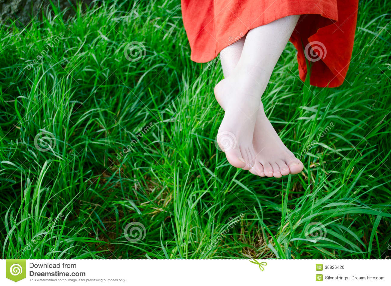 Young womans feet amongst green grass in nature