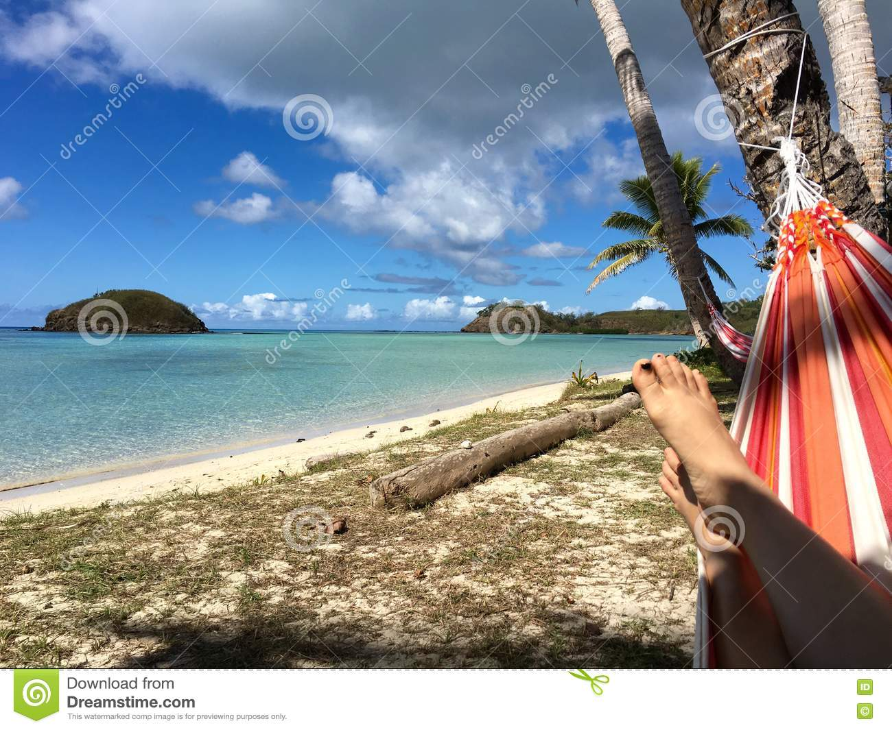 Relaxing under coconut trees shade on colourful hammock
