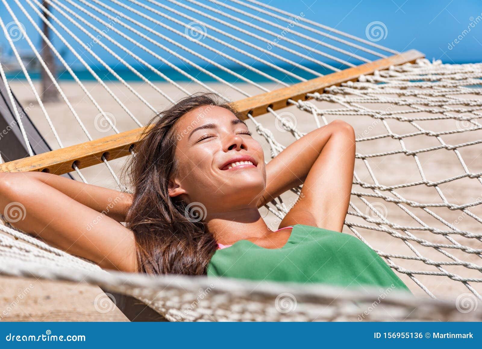 Relaxing woman sleeping on hammock in the tropical sun. Asian girl resting lying down in resort lounger laid back enjoying suntan