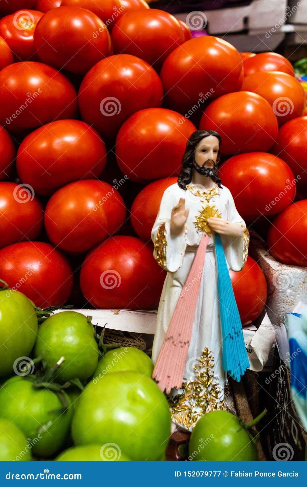 Religiöse Figur mitten in den roten und grünen Tomaten an einem Marktstall