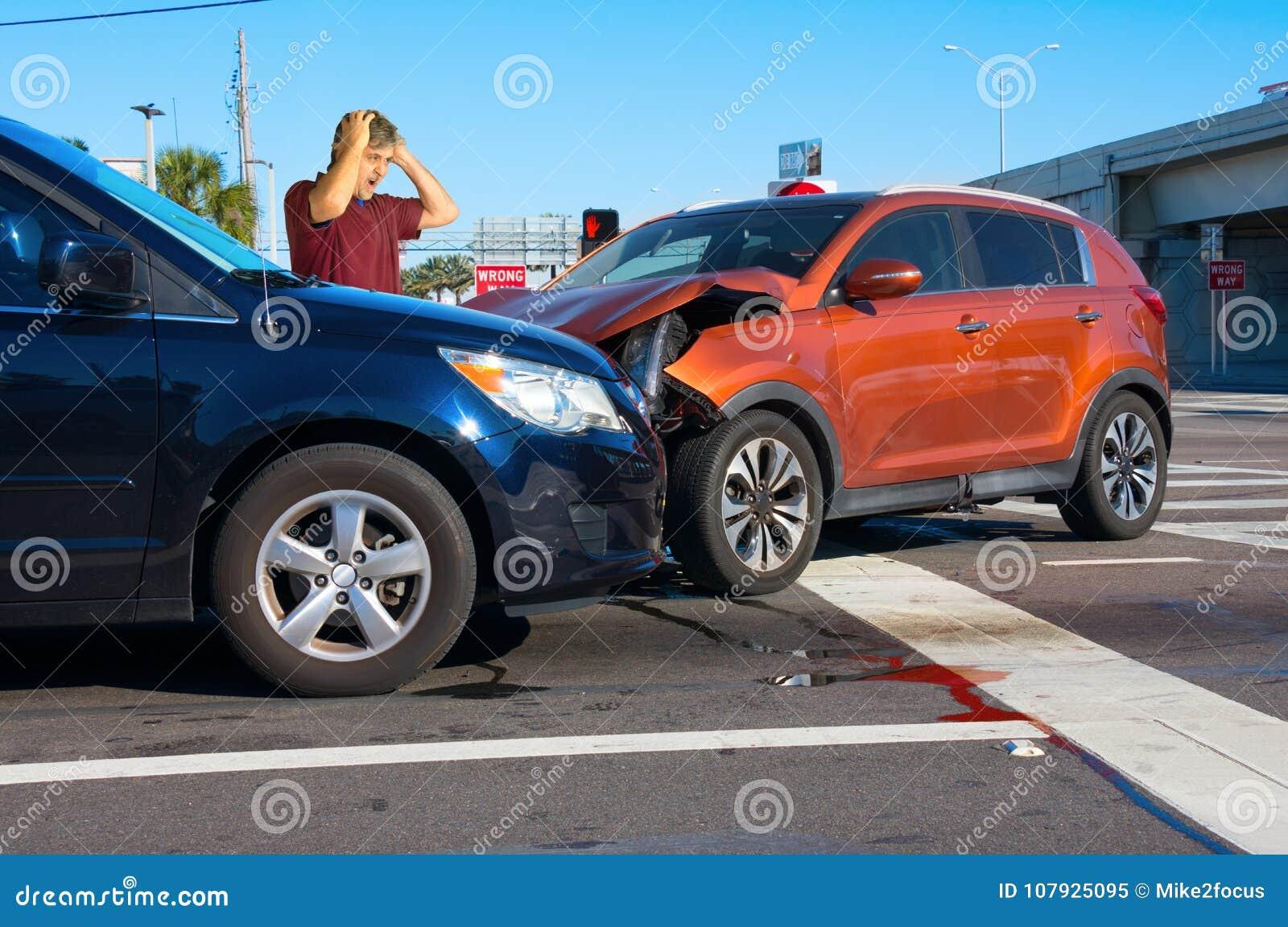 Relitto serio dell automobile all intersezione con l autista molto turbato dell uomo che esamina danno