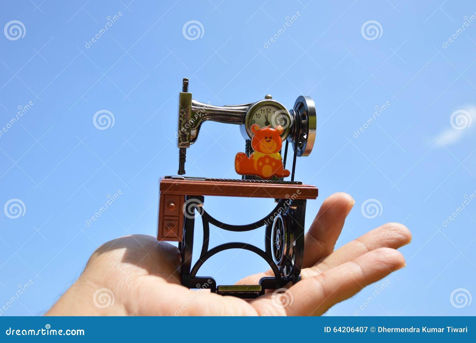 Reloj Antic de la máquina de coser en la palma con el cielo azul