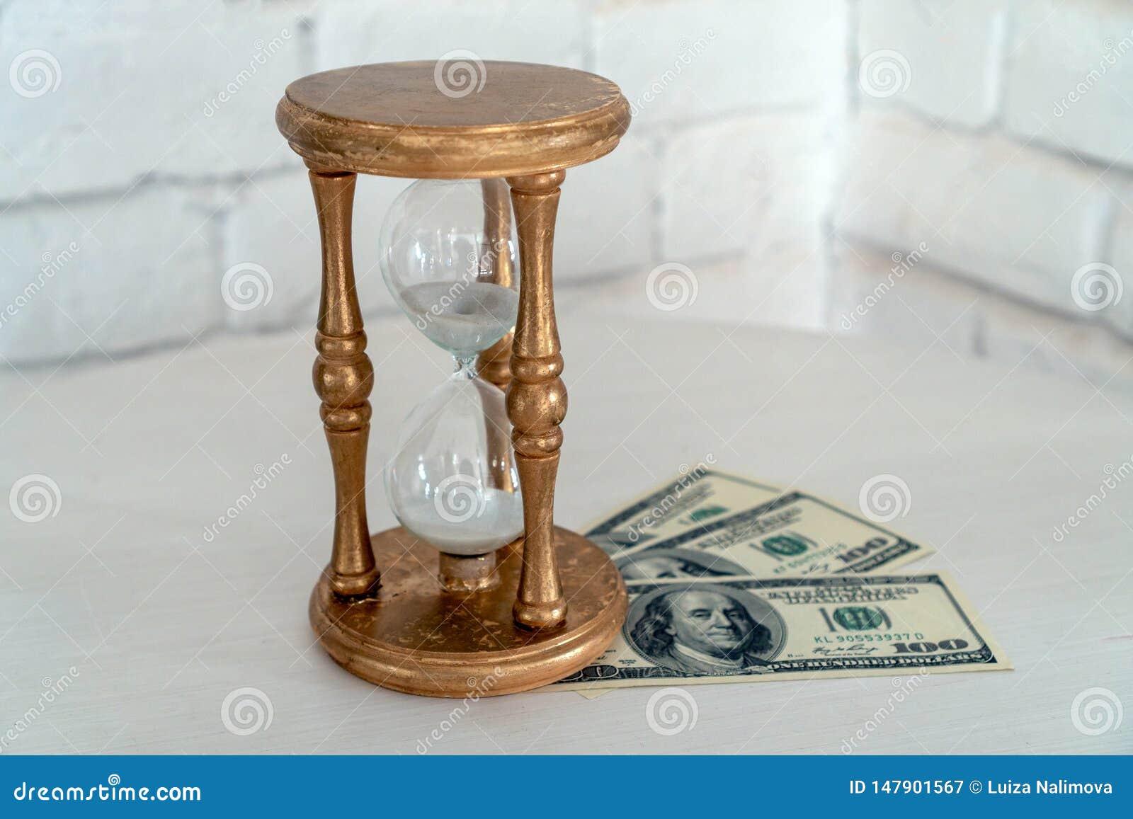 Reloj de arena y dinero de madera en un fondo blanco El concepto del tiempo es oro