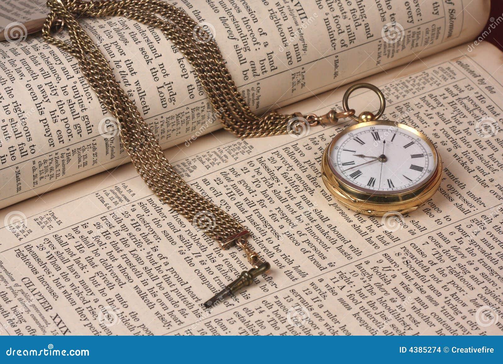 Reloj de bolsillo del oro en la biblia vieja
