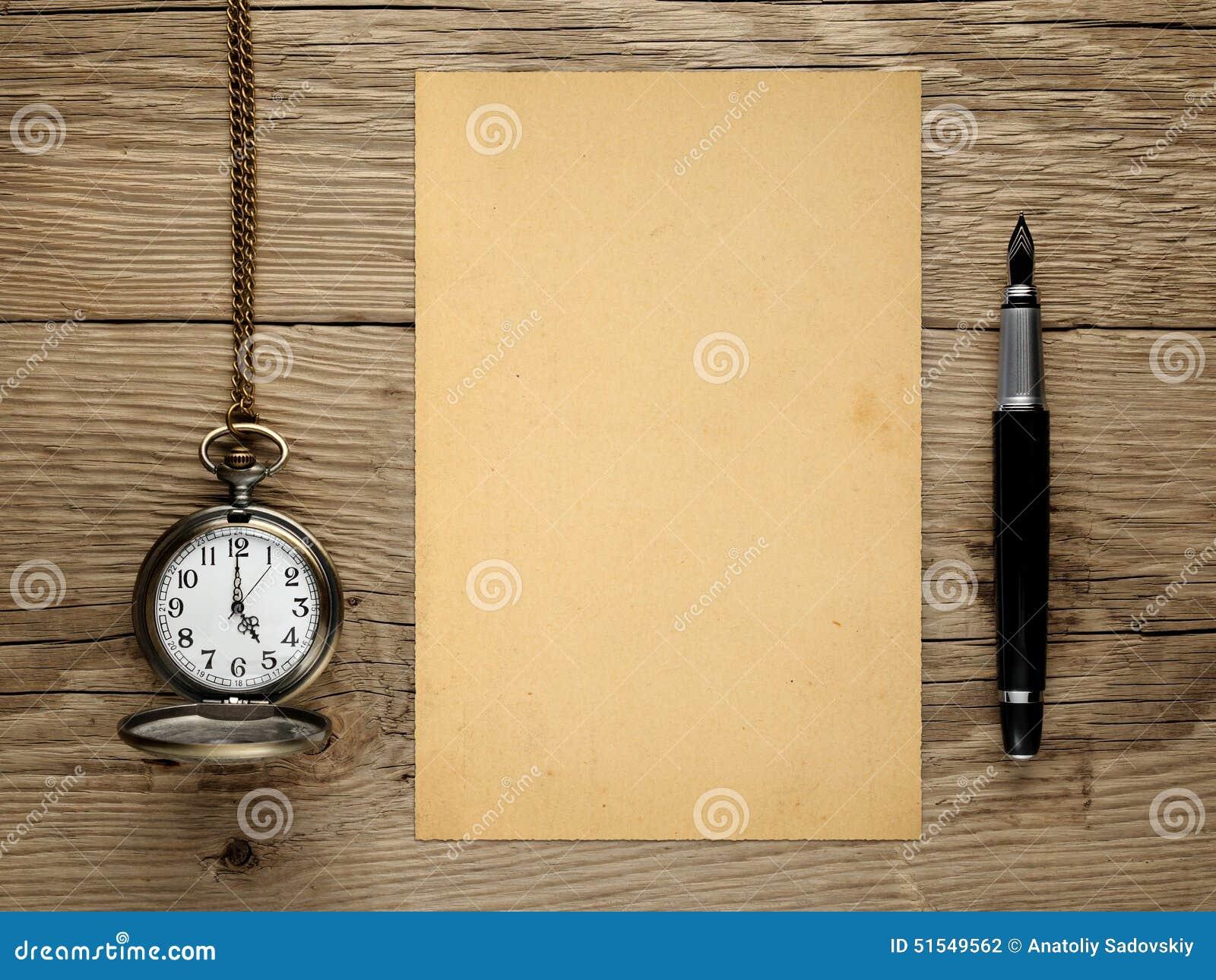 Reloj de bolsillo, pluma y papel viejo