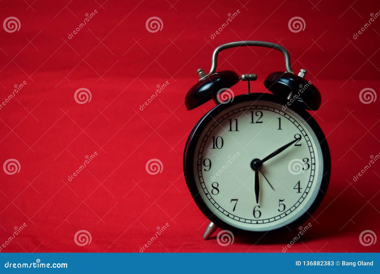Reloj que hace tictac a las 6 en el fondo rojo