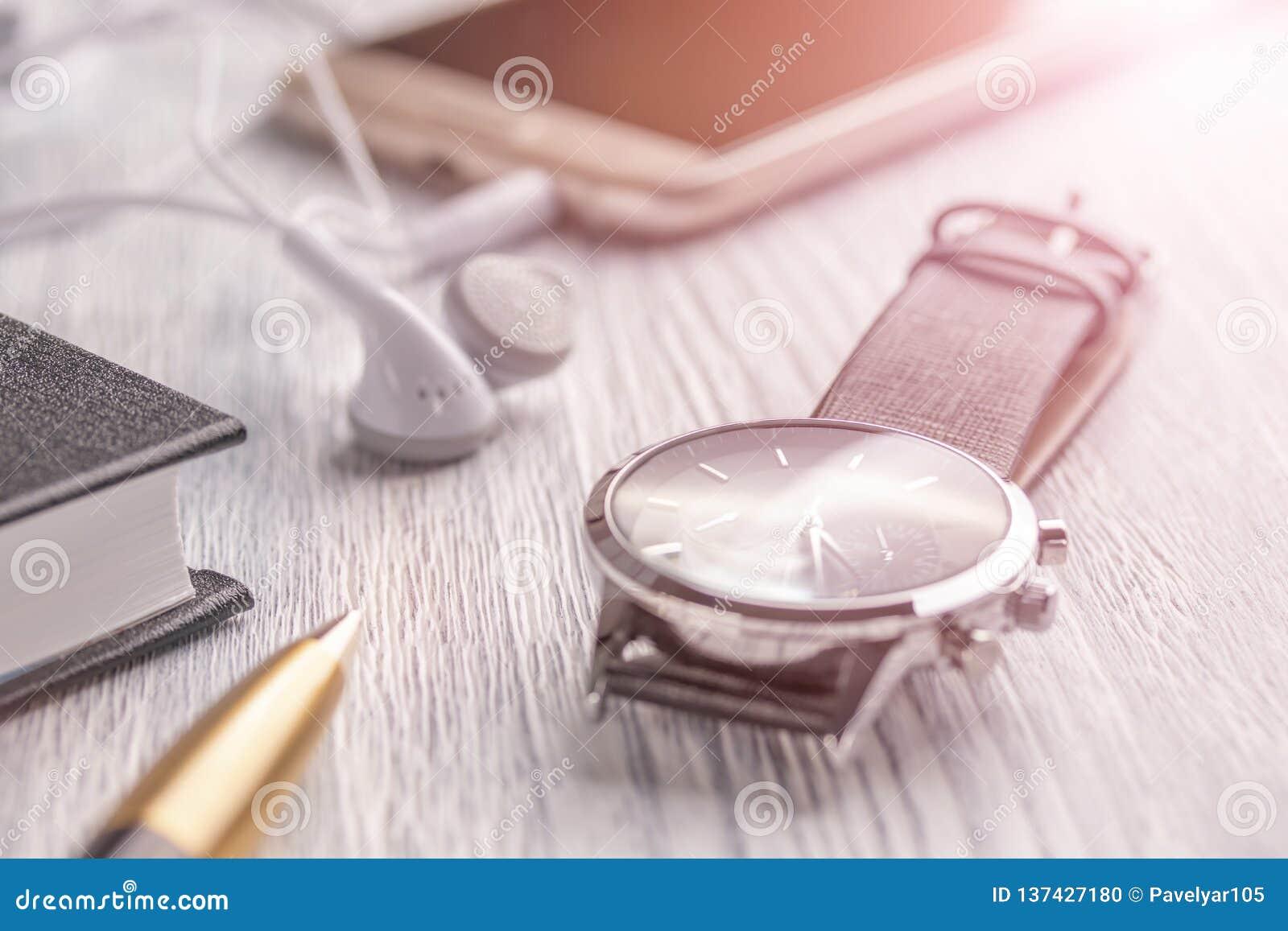 Reloj, teléfono móvil con los auriculares y un cuaderno con una pluma en una mesa y un café blancos viejos de la oficina
