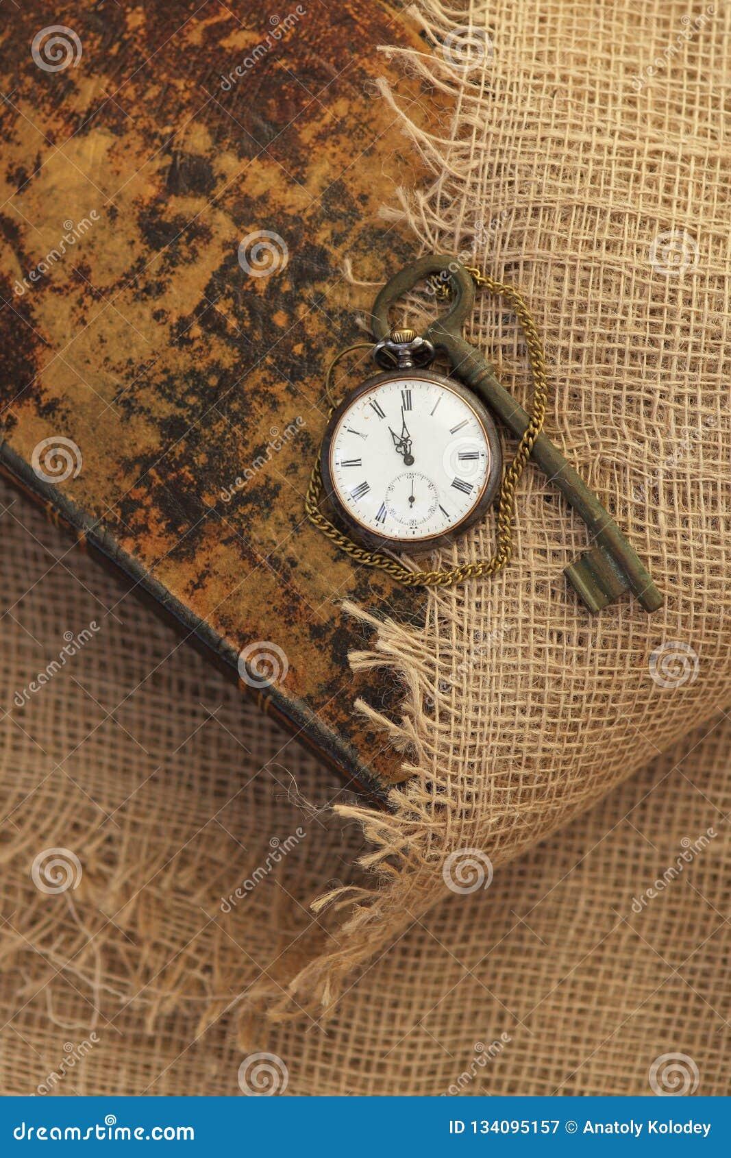 Reloj y llave de bolsillo antiguo en el folio viejo mitad-cubierto con harpillera vieja Tiempo que pasa concepto Concepto de la e