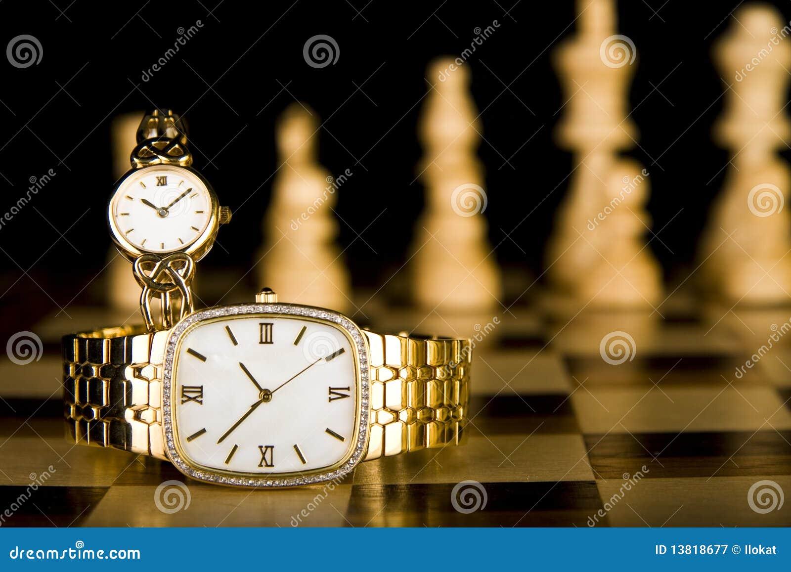 Relojes de oro en tarjeta de ajedrez