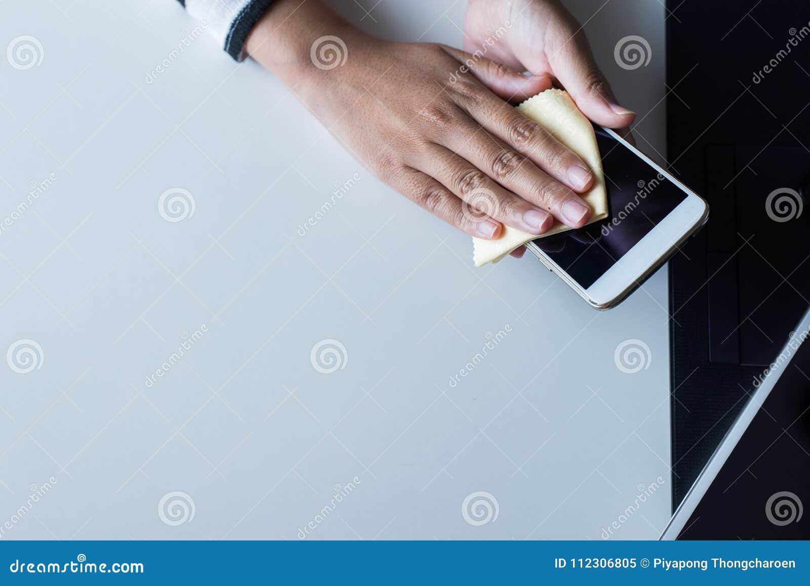 Remettez la femme nettoyant le téléphone intelligent sur l écran avec le tissu de microfiber
