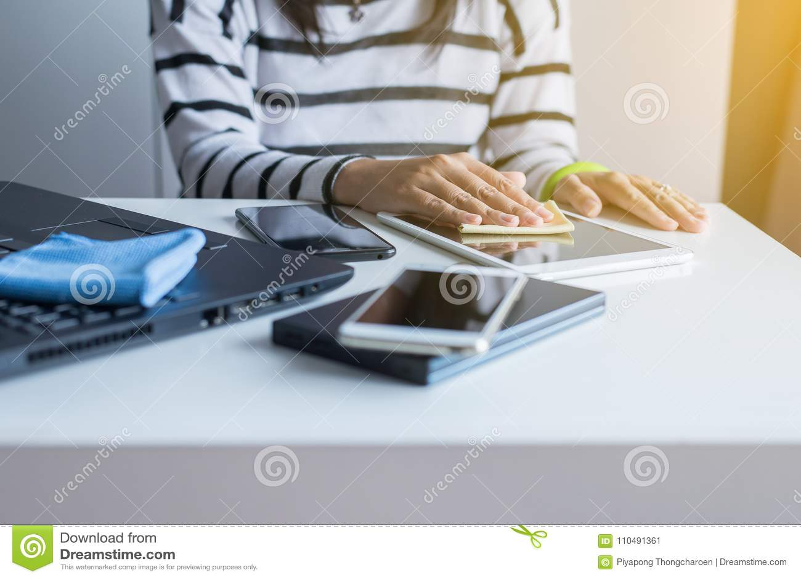 Remettez la femme nettoyant son comprimé sur l écran avec le tissu de microfiber