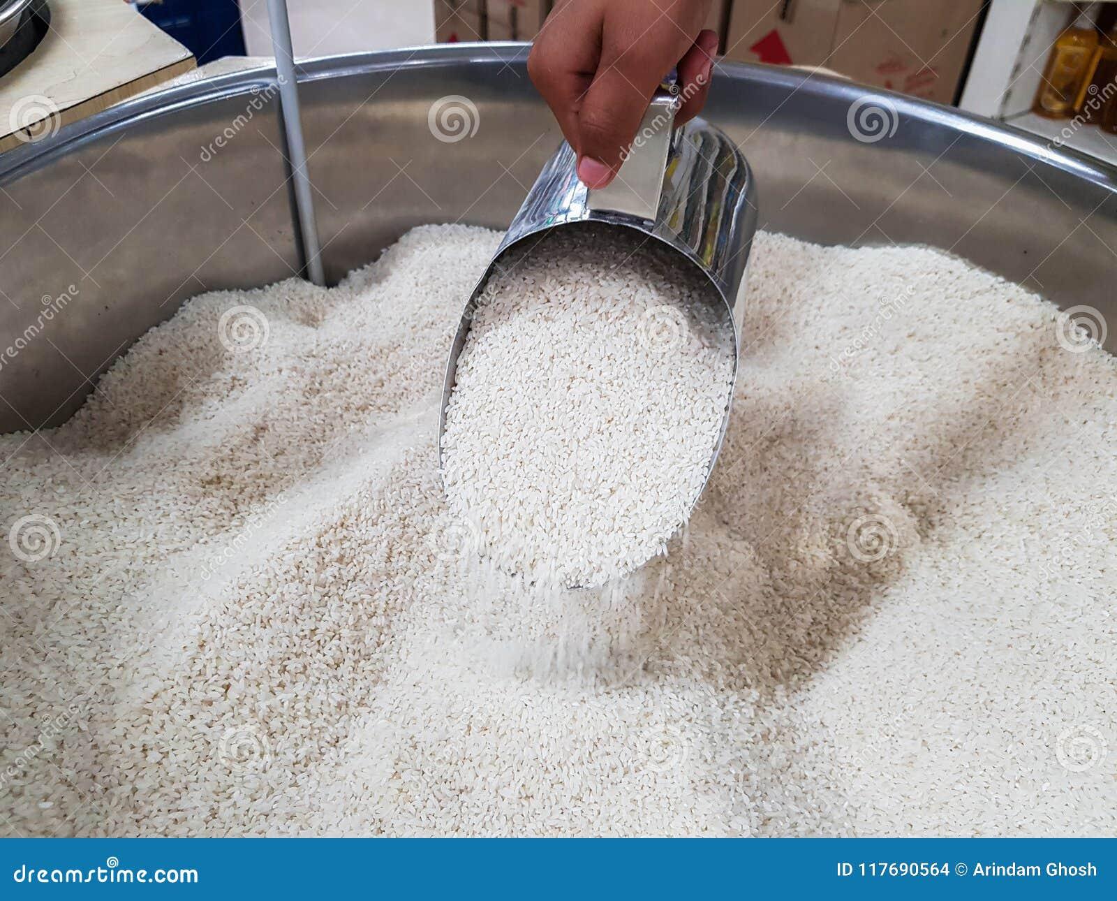 Remettez le tas cru cru de versement du riz avec le récipient de distribution de mesure de tasse au supermarché à vendre