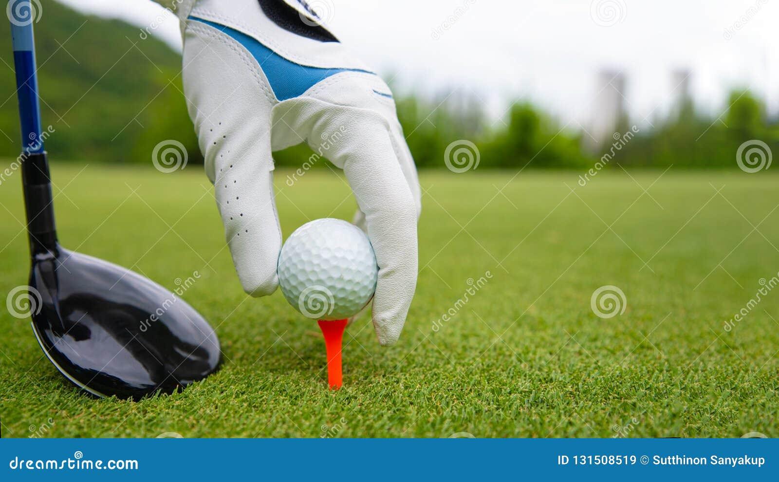 Remettez mettre la boule de golf sur la pièce en t dans le terrain de golf