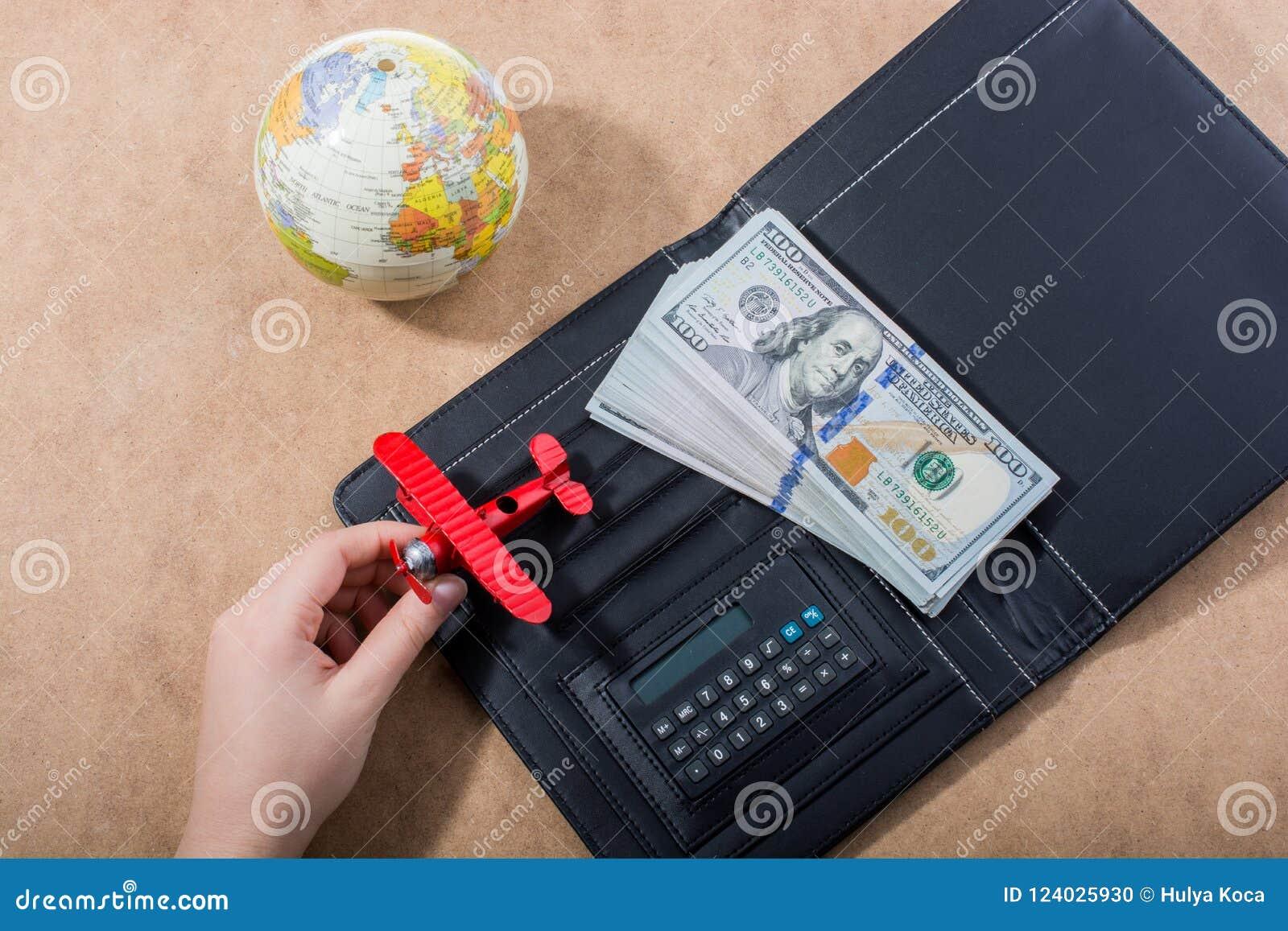 Remettez tenir l avion modèle près du globe et des dollars
