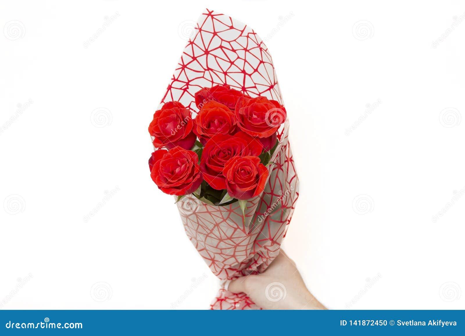 Remettez tenir le bouquet des roses rouges au-dessus du fond blanc