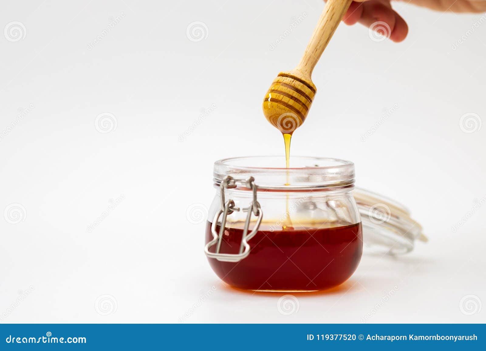 Remettez tenir un dispositif d écoulement de miel sur le fond blanc Concept de nourriture