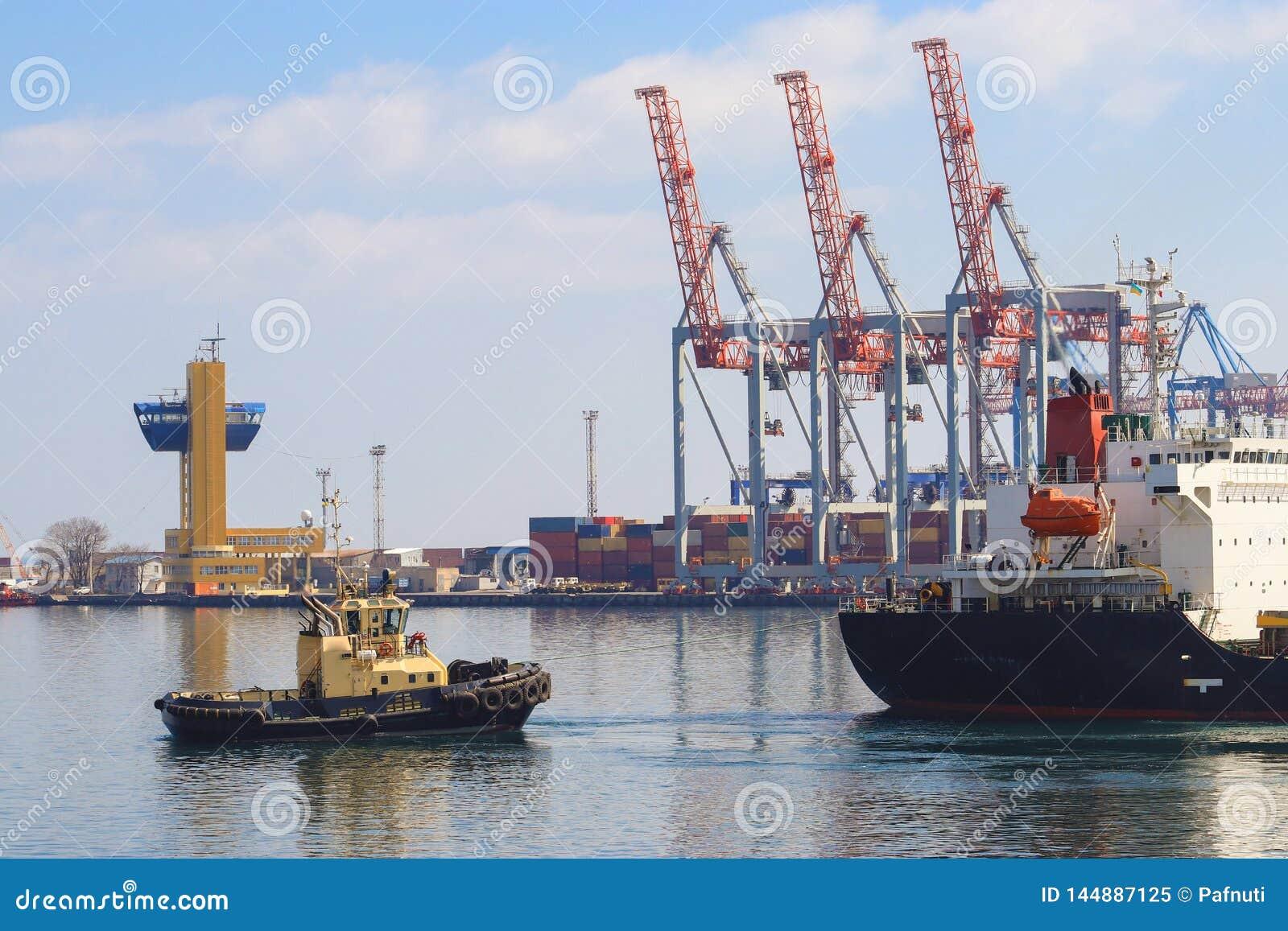 Remolcador que ayuda al buque de carga maniobrado en el puerto de Odessa, Ucrania