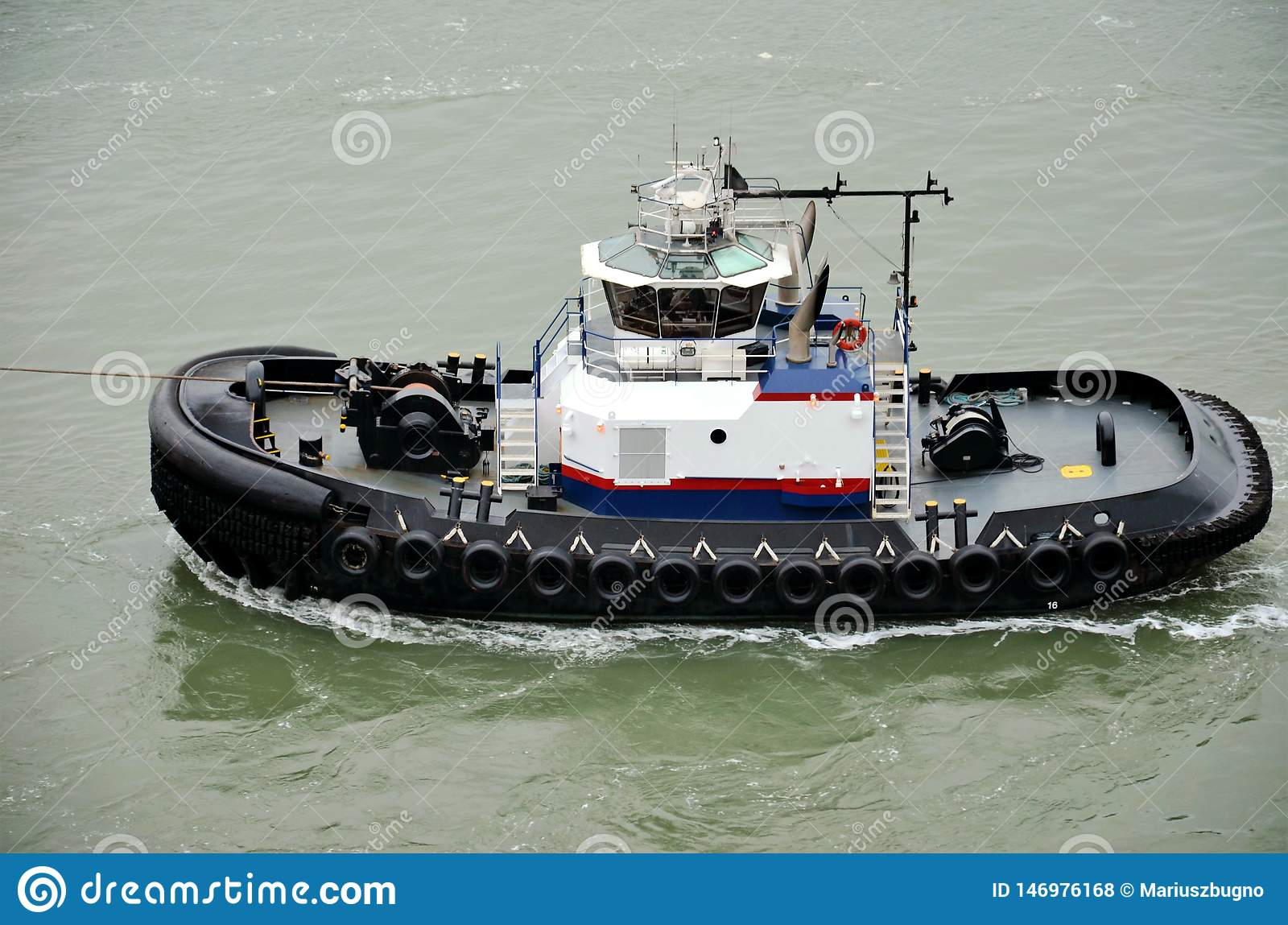 Remolcador que ayuda con atracar del buque de carga, bahía de Nueva York