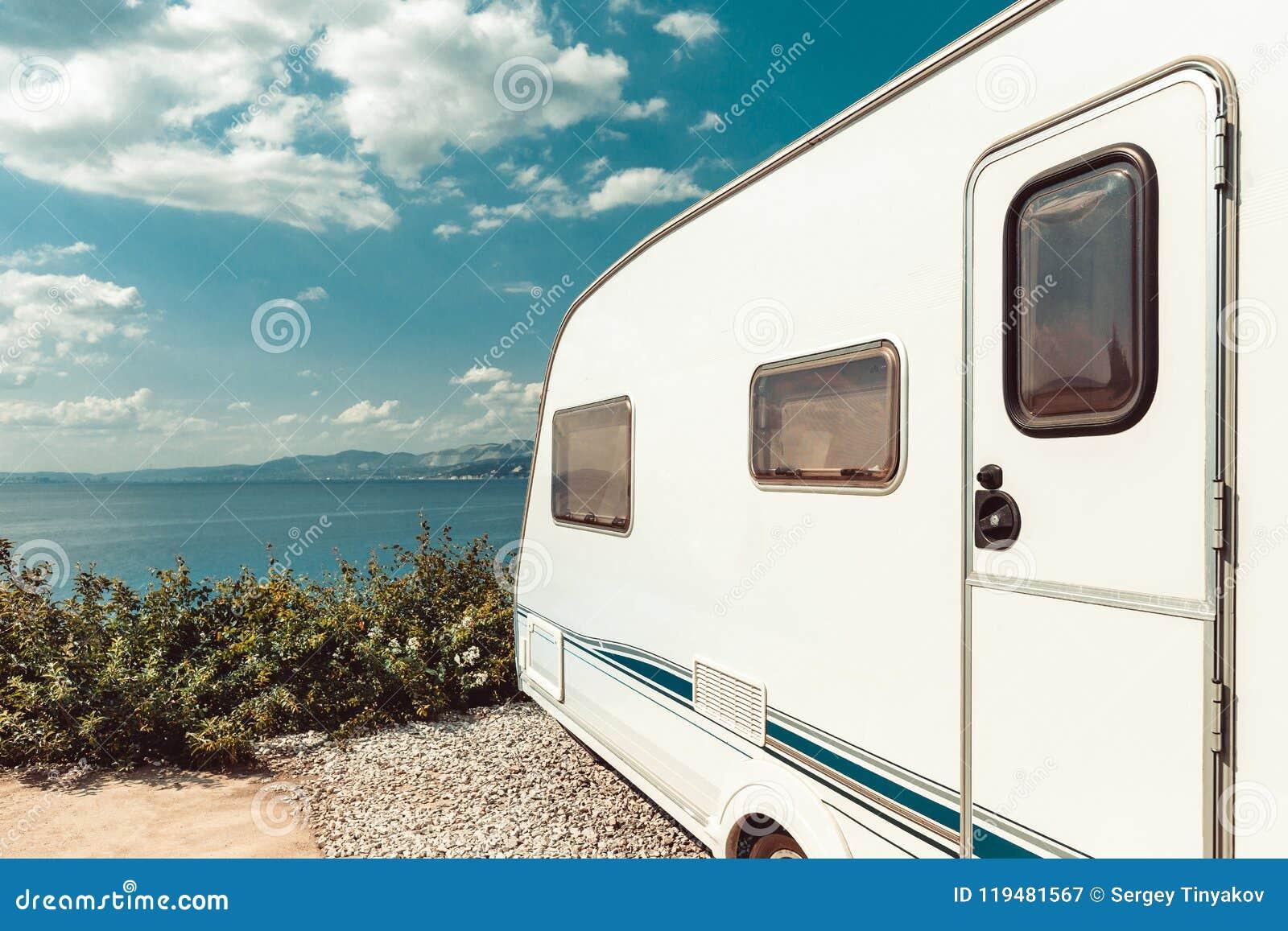 Remolque de la caravana cerca del mar, de la playa y del cielo azul Ro de las vacaciones de verano