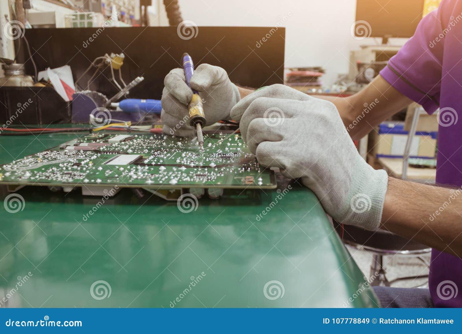 Remontowy mężczyzna używa cyfrowego multimeter pomiar na obwodzie PCB deska