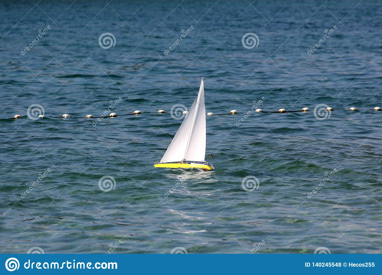Remote controlled yellow sailing boat with clear white sails used as children toy in local bay on restless sea surrounded with