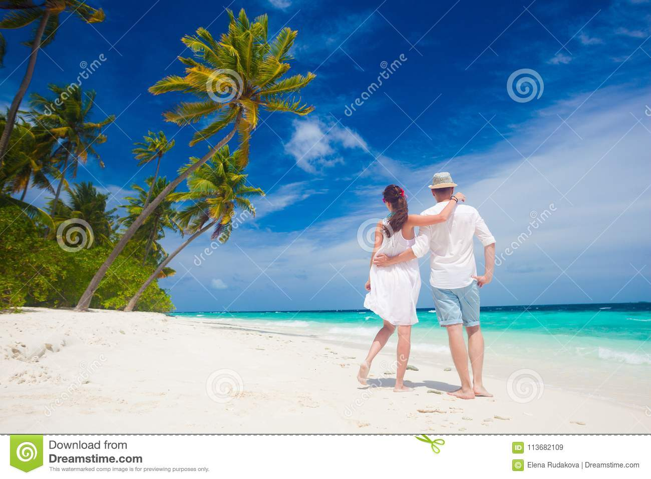 happy young couple in white clothes walkingthe beach. maldives