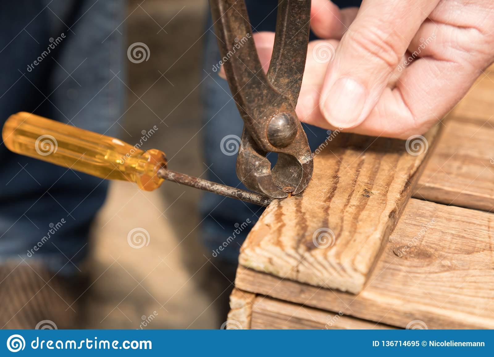 Remove a nail with a pair of pliers